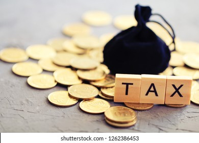 """Word """"tax"""" and black bag on coins. Tax concept."""