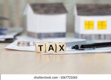 Word TAX composed of wooden letters in front of handmade house. Closeup