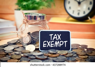 Word Tax Exempt on mini chalkboard and coin in the jar with blurred background of books, green plant and clock. Financial Concept.