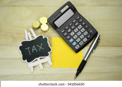 Word tax on blackboard with coins, calculator and pen