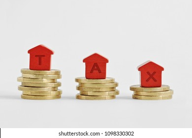 The word Tax written with miniature houses on top of coins - Home taxes decrease concept