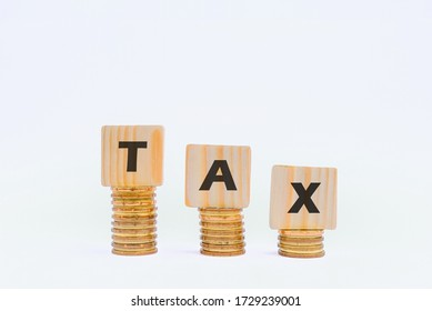 Word TAX written on wooden cubes on stacked coins isolated on white. TAX CONCEPT