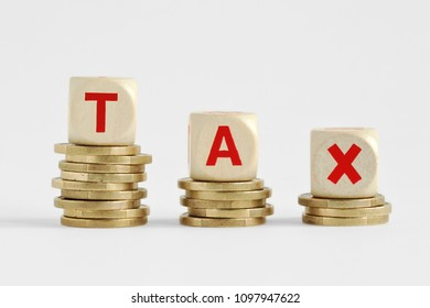 The word Tax written with wood blocks on top of coins piles - Tax decrease concept
