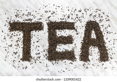 """The word """"TEA"""" written with Gunpowder green tea leaves, on marble background."""