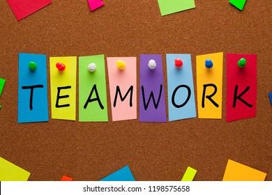Word TEAMWORK written on colorful stickers pinned on cork board.