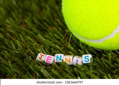 The word tennis is made up of cubes with colored letters lying on the green grass next to the tennis ball