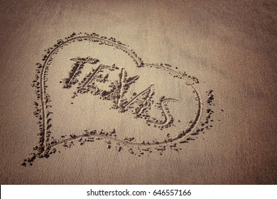 The word Texas and heart drawn on the beach sand. Love Texas concept.