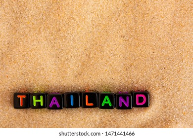 The word Thailand is made up of colored letters on black cubes on sand