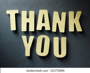 The word Thank you in cut out paper letters on paper background