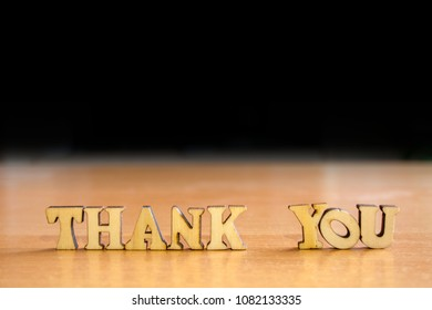 The word 'thank you' made of wooden letters. wood inscription on table and dark black background