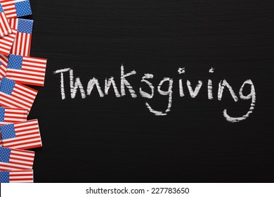 The word Thanksgiving written by hand on a blackboard alongside miniature stars and stripes flags of the United States of America.
