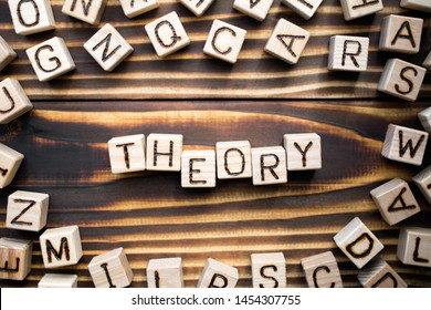 word theory composed of wooden cubes with letters, explain a fact or event concept, scattered around the cubes random letters, top view on wooden background