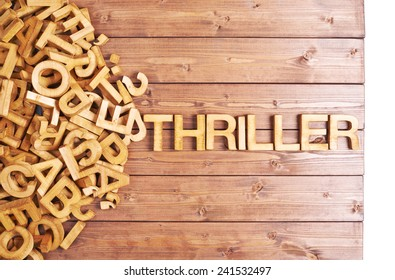 Word thriller made with block wooden letters next to a pile of other letters over the wooden board surface composition