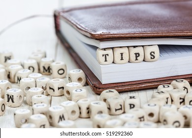 Word Tips written on a wooden block in a book. On old white wooden table.
