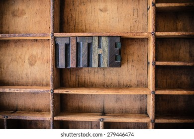 The word TITHE written in vintage wooden letterpress type in a wooden type drawer.