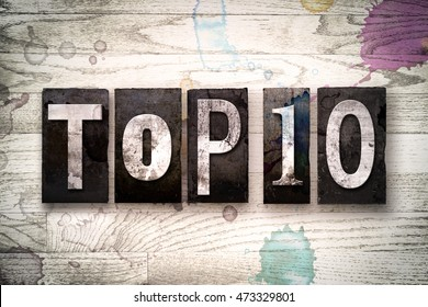 "The word ""TOP 10"" written in vintage dirty metal letterpress type on a whitewashed wooden background with ink and paint stains."