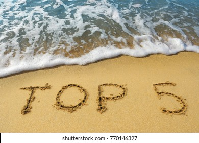 """The word """"top 5"""" is written on the golden sand of the beach by the sea. Concept - the five best beaches, tours or ways to relax in the south."""