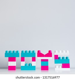 word toys folded of toy constructor and copy space over wall background