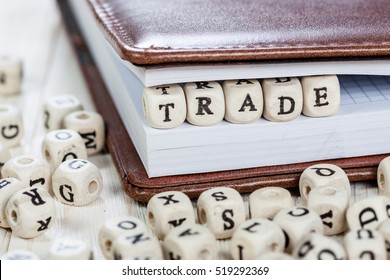 Word Trade written on a wooden block in a book. On old white wooden table.