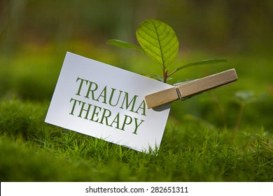 "The word ""Trauma Therapy"" with a seedling"