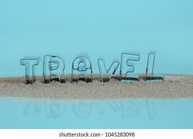 Word TRAVEL made of cookie cutters and sand isolated on blue background
