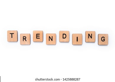 The word TRENDING, spelt with wooden letter tiles over a white background.