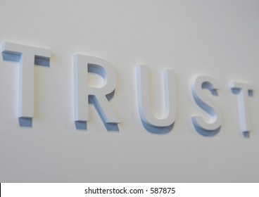 """The word """"trust"""" embossed on a white wall, partially blurred embossed"""