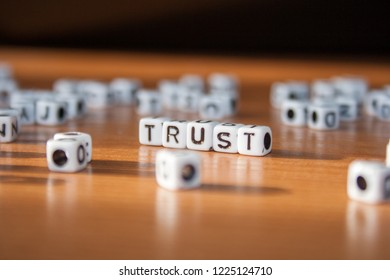 The word TRUST made of white plastic blocks on the table. Letter concept.