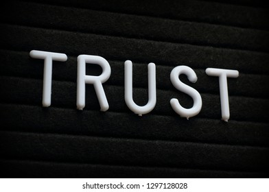 The word Trust in white plastic letters on a black letter board