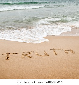 Word truth written on the sand near the sea. Sea waves rolling onto the beach.