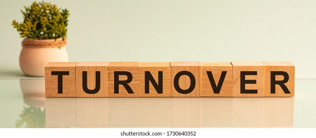 Word TURNOVER is made of wooden building blocks lying on the table and on a light grey background. Concept