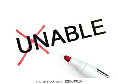"The word ""UNABLE"" is written in black letters on a white background. Red marker crossed out ""UN"""