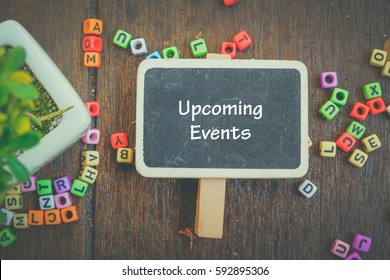 word UPCOMING EVENTS on wooden signage,artificial plant and alphabetical block concept.fade color effect