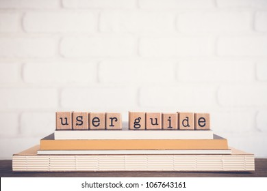 The word User guide, text on wooden cubes on top of books. Background copy space, vintage minimal. Concepts of manual or technical communication document to give assistance about using system.