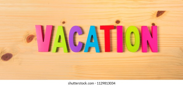 Word vacation in colorful letters on wood