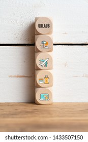 "Word ""Vacation"" in German depicting online travel concept with a row of wooden blocks with travel icons"