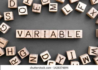 the word variable wooden cubes with burnt letters, variable life, gray background top view, scattered cubes around random letters