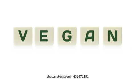 """Word """"Vegan"""" on board game square plastic tile pieces, isolated on a white background."""