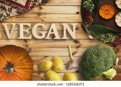 """Word """"vegan"""" in wooden letters with many cooking ingredients on wooden background"""