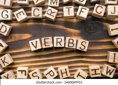 word verbs composed of wooden cubes with letters, Part of speech concept scattered around the cubes random letters, top view on wooden background