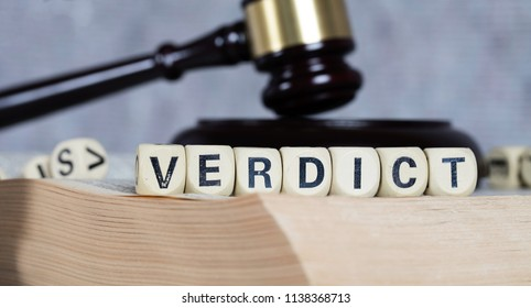 Word VERDICT composed of wooden letters. Statue of Themis and judge's gavel in the background