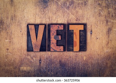 "The word ""Vet"" written in dirty vintage letterpress type on a aged wooden background."