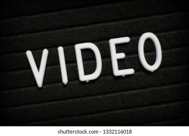 The word Video in white plastic letters on a black notice board