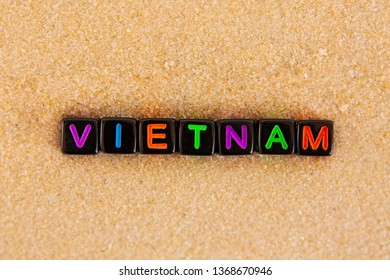 The word Vietnam is made up of colored letters on black cubes on sand