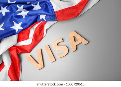 Word VISA and American flag on grey background