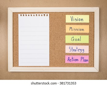 "Word ""Vision Mission Goal Strategy Action Plan"" and blank notepad on cork board (Business concept)"