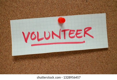 The word Volunteer written by hand in red ink on a piece of graph paper and pinned to a cork notice board