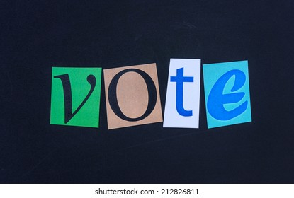 The word vote in cut out magazine letters on blackboard