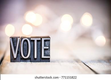 The word VOTE written in vintage metal letterpress type on a bokeh light and wooden background.