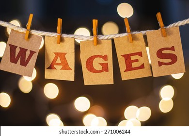 The word WAGES printed on clothespin clipped cards in front of defocused glowing lights.